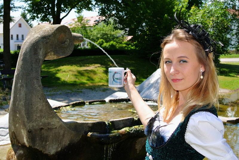 Maria Weiss mit der Puchheim-Tasse vor dem Dorfbrunnen in Puchheim-Ort. Foto: Markus Limbacher