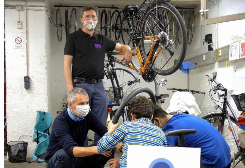 Das Foto zeigt Bürgermeister Norbert Seidl (Foto links) mit zwei Kindern beim Reparieren eines Reifens sowie Bernd Moraweck (Foto hinten), den Leiter der Radlwerkstatt.