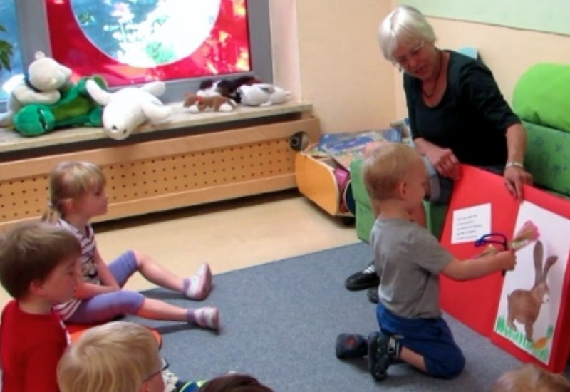 Sprachfachkraft Ursula Lävemann mit Kindern der Mäusegruppe beim Vorlesen