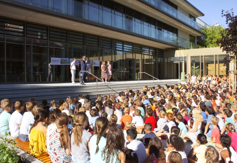"""Die 500 Schülerinnen und Schüler der Grundschule am Gernerplatz warten gespannt auf die Preisverleihung der Aktion """"Zu Fuß zur Schule""""."""